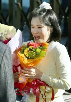Keiko Aoki chora ao receber flores após deixar penitenciária em 26-10-2015 (Foto: Kyodo)