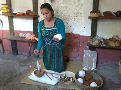Mujeres locales explican la técnica de crear bolas de hilo para luego teñirlas.