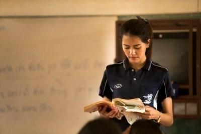 Teacher holding tattered lesson book
