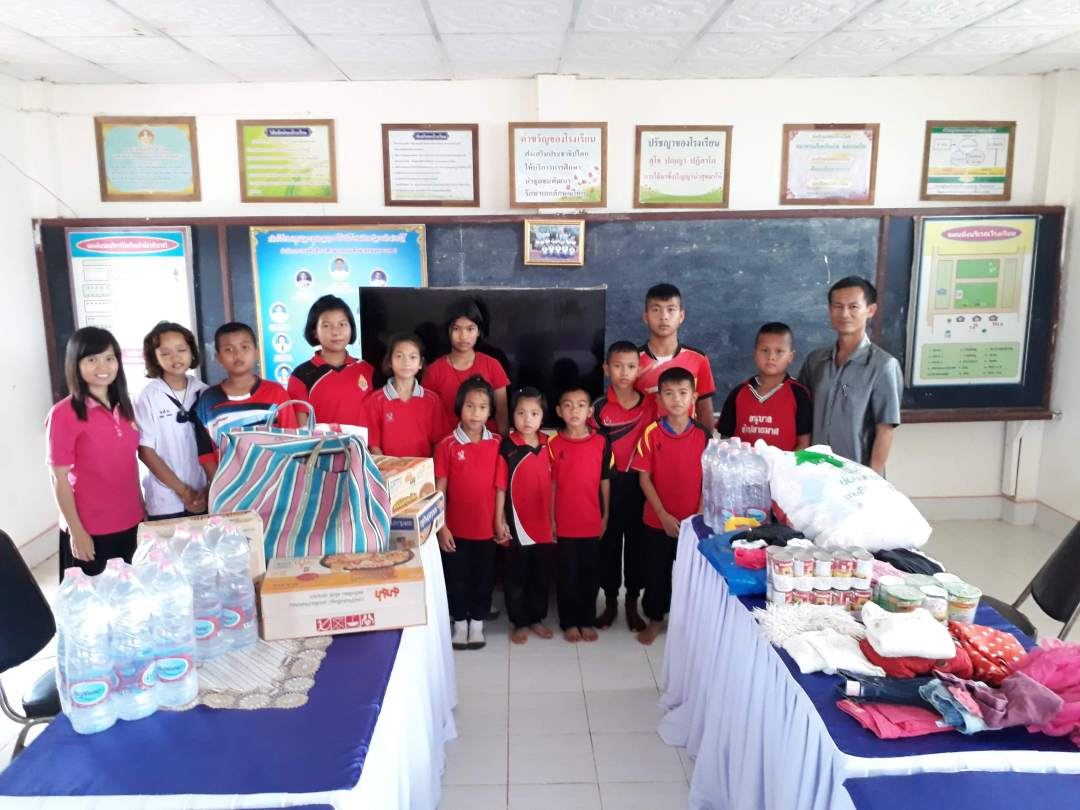 thai students and teacher pose with food, water and clothing