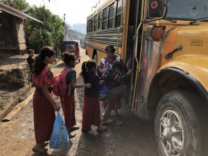 young kids in Guatemala loading the schoolbus in Chajul