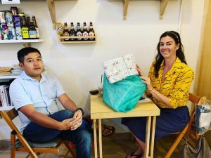 Mundo member Kayla and local donor giving diapers at a coffee shop