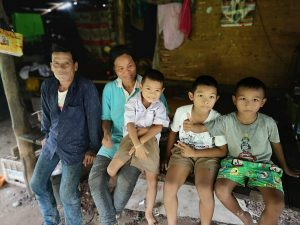 Nuan and her family sit on a bench in their home in rural Thailand