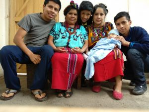 Juana and her family sit together in their new kitchen