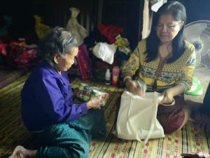 Ra Ruay sits on the floor with local volunteer Suwannee with a care package