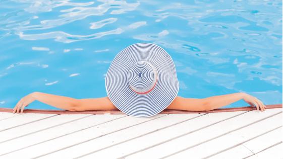 mulher de chapéu aproveitando o dia na piscina