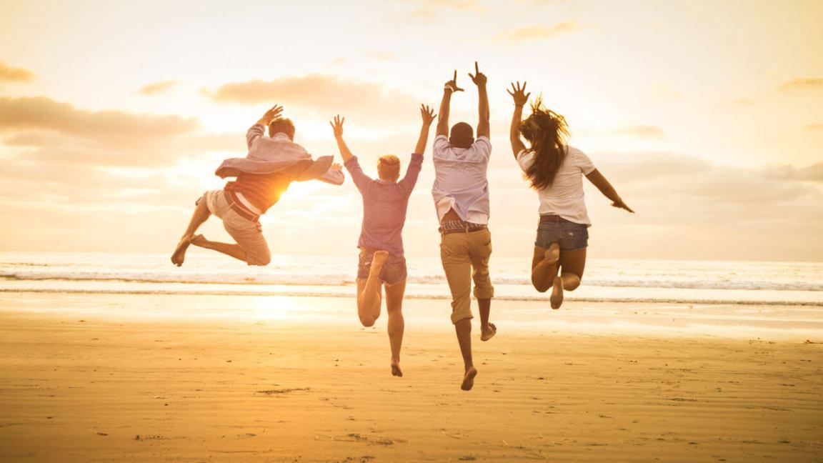 quatro amigos felizes pulando e se divertindo na praia