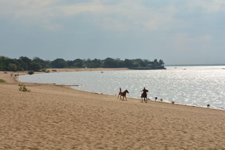 Garoto treina seu cavalo na praia de Paso de la Pátria