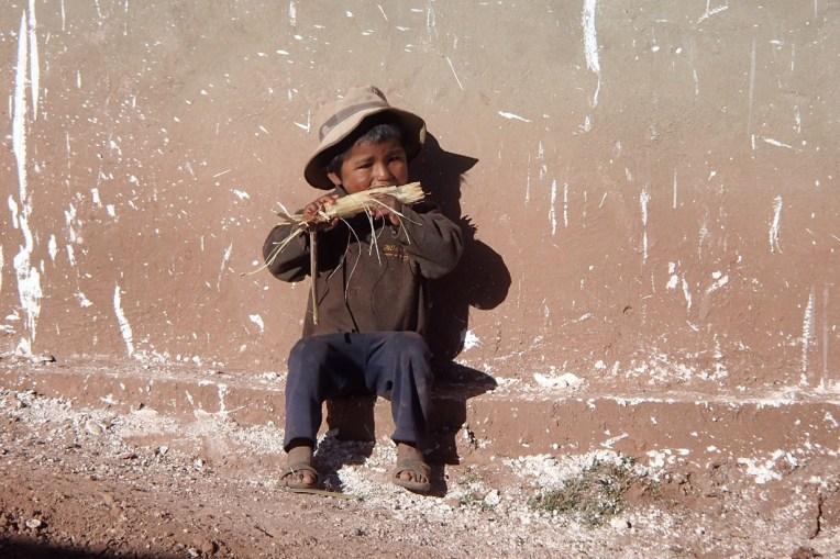 Menino chupando cana em Macha depois do Tinku