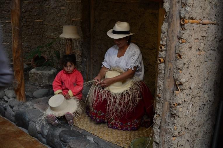 """Uma """"chola"""" cuencana e sua filha confeccionando um chapéu do Panamá"""