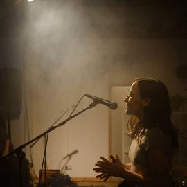 Gründerin Gina Maria Mund spricht am Mikrofon zu Konzertbesucher*innen