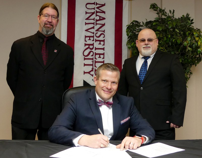 President Scott Barton prepares to sign agreements with Huaqiao University, Shandong University, and Southwest Petroleum University as Provost John Ulrich (left) and Brad Lint (right), US-China exchange coordinator and assistant professor of English, look on.
