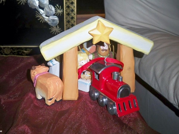 Train ornament pulling baby Jesus coach with sheep on top through manger/tunnel while all other figures following behind