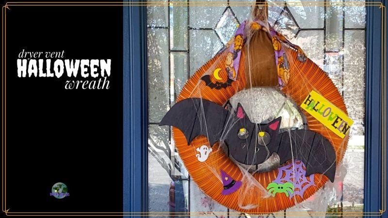"Halloween wreath on a doow with text overlay ""dryer vent Halloween wreath"""