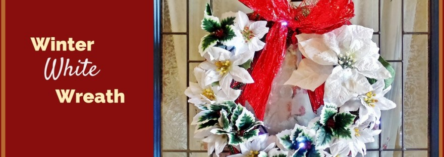 This Winter White Wreath features glitter covered silk poinsettias and contrasting green and red holly sprigs to greet family and friends this Christmas.