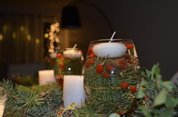 candle floating in a glass of greenery