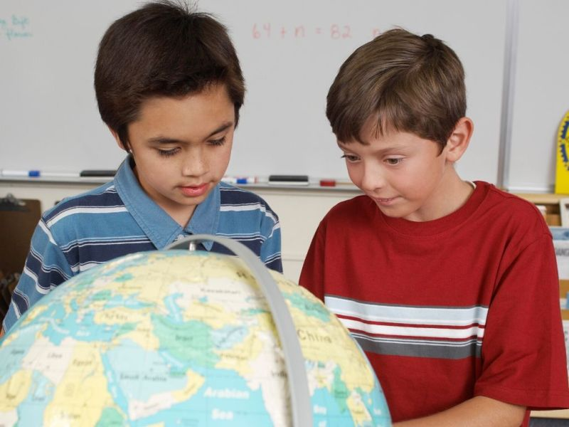 two boys studying a globe