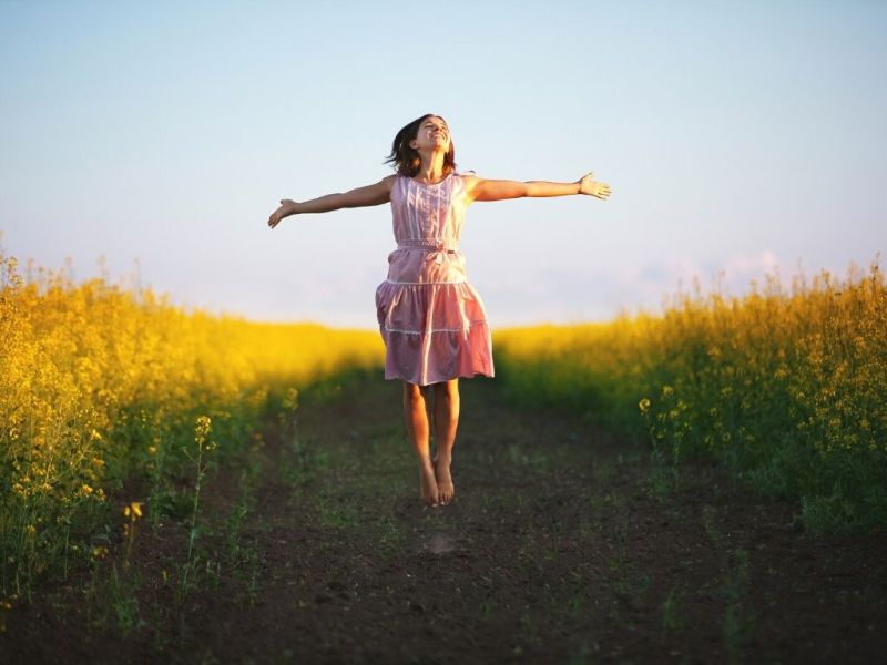 joyful woman with outstretched arms on a path in the middle of yellow wildflowers - kids with Autism need friends