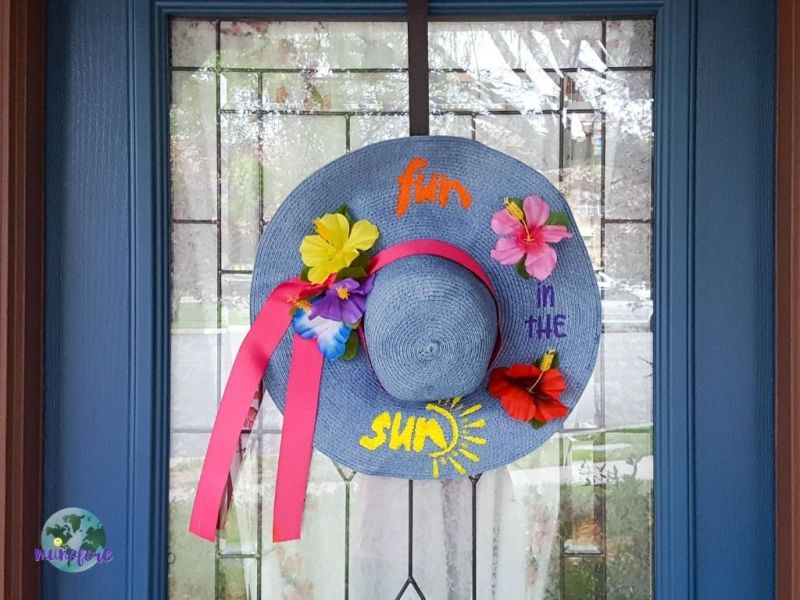decorated sun hat hanging on a front door