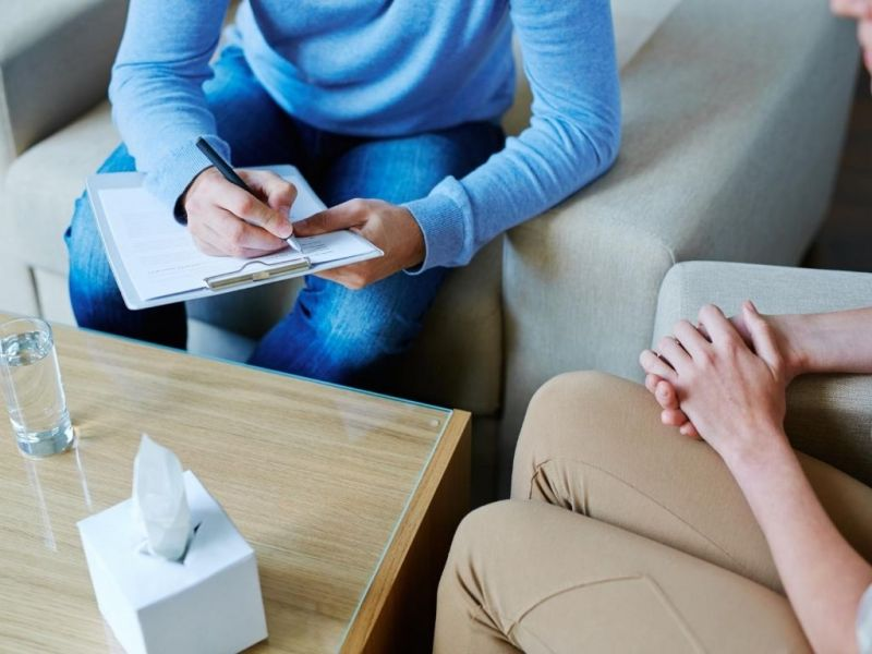 two people sitting at a table with one taking notes
