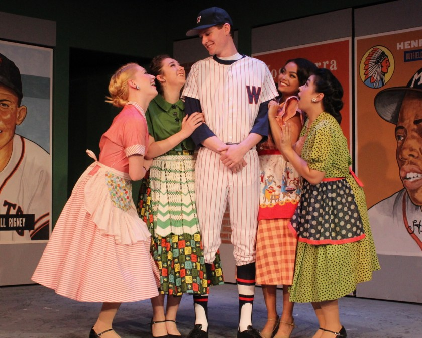 Four fans surround baseball great Joe Hardy, played by Tim Smith, in the Good Company Players production of 'Damn Yankees.'
