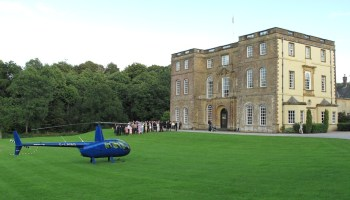 Blue helicopter is parked on the lawn of a large country house, group of guests in background
