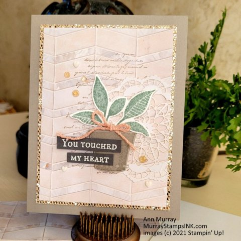 succulent foliage in a pot on a chevron marble tile background