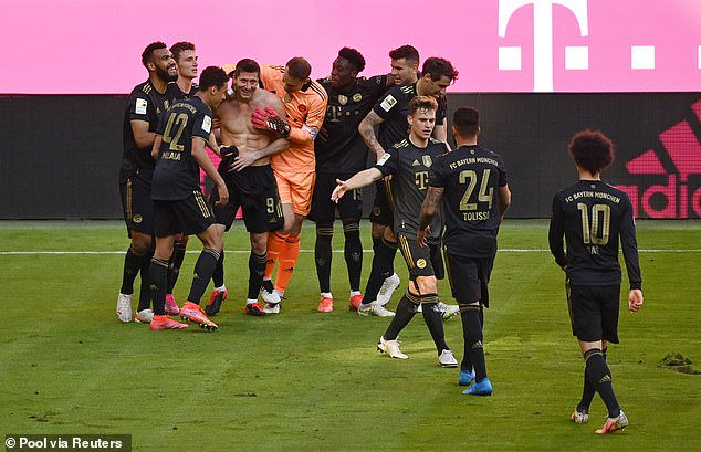 The Polish striker is mobbed by his Bayern team-mates after his record-breaking strike