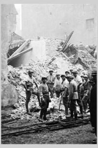 Photographie des secouristes de lyon Saint Jean. Derrière eux, la terre arrive jusqu'au milieu des immeubles.