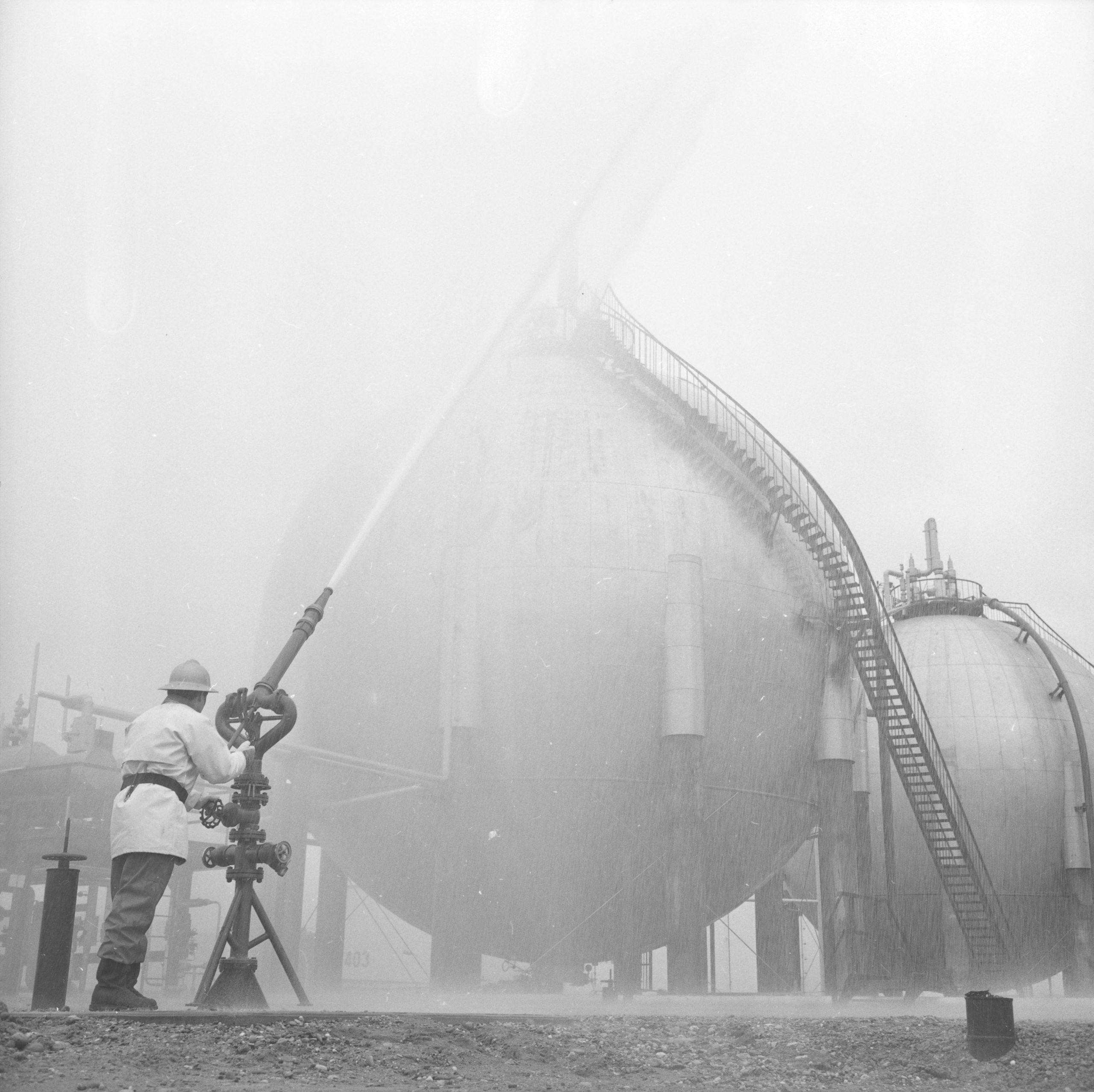 Photographie de la raffinerie de Feyzin : deux sphères contenant les produits chimique sont arrosées par la lance à incendie d'un sapeur-pompier. Photo par George Vermard