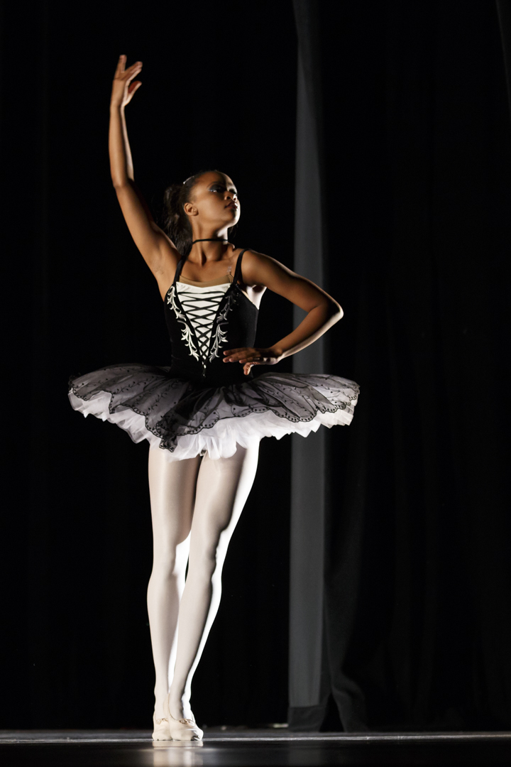 teen ballerina in a black and white costume posing on stage