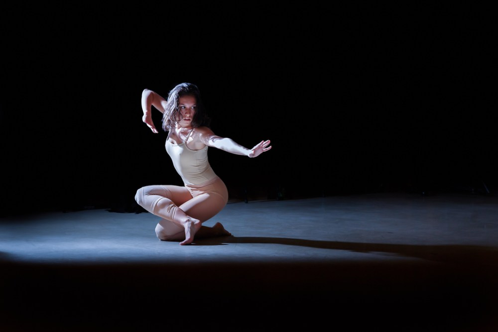 female dancer crouches in a pose in a spotlight