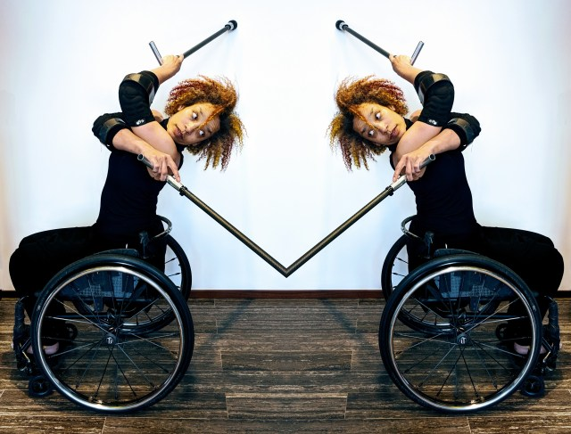 Alice Sheppard seated in her wheelchair with two crutches, crosses her body and arches her spine to look behind. The photo is a mirror reflection and Alice looks back at herself as her crutches disappear into each other in a seamless touchpoint. Photo by Lisa Niedermeyer
