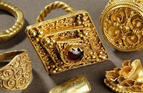 A photograph of 5 ornate gold rings. The middle one is the largest, and has a ruby in the middle.