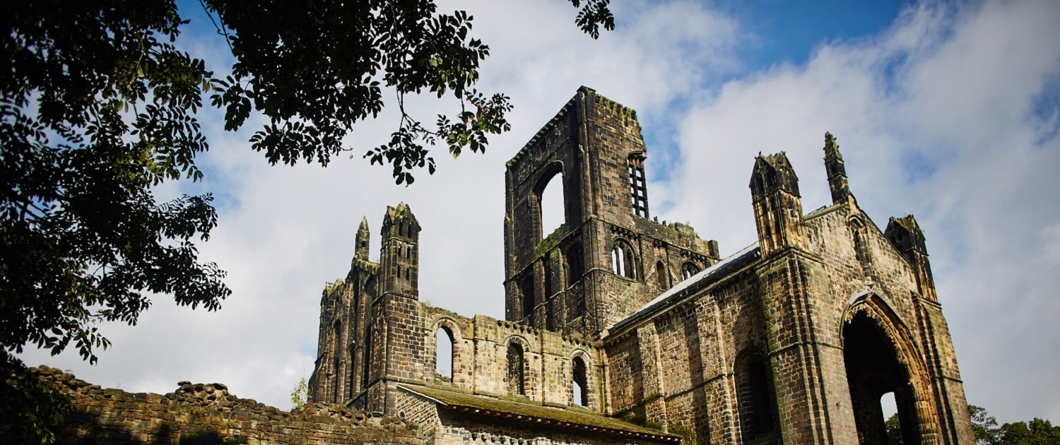 Kirkstall Abbey ruins shot from the ground, next to a tree