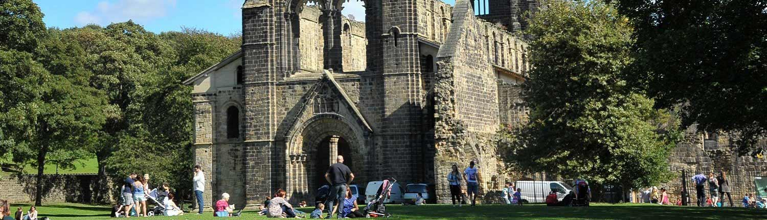 Several groups of people sitting and standing in front of Kirkstall Abbey