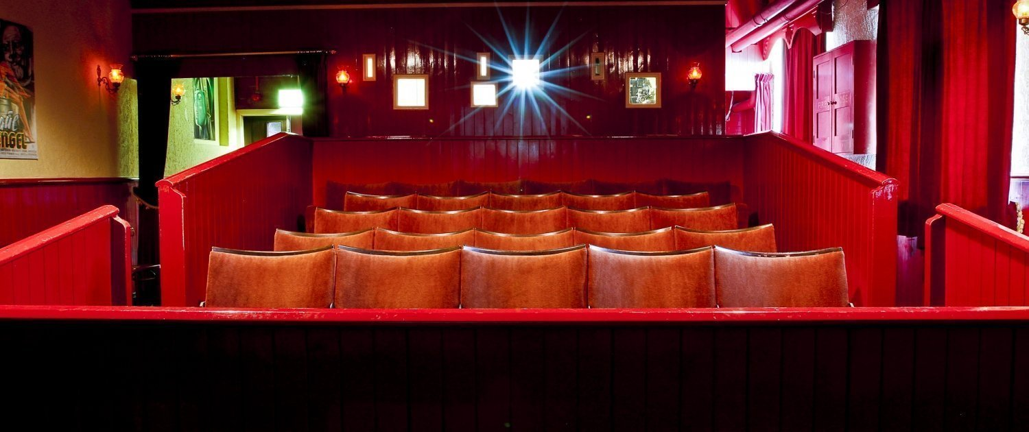 Four rows of seats in an old fashioned cinema