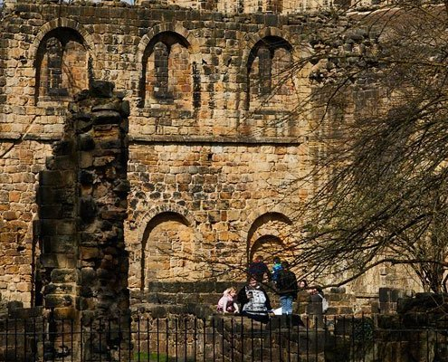 A family are having fun, sitting on the ruins of Kirkstall Abbey.
