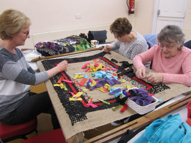 Image of volunteers working on the traditional rag rug on display