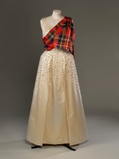 Norman Hartnell, Evening dress of embroidered duchesse satin worn by TheQueen with a sash of Royal Stewart tartan for the Gillies Ball at Balmoral Castle in 1971. ROYAL COLLECTION TRUST/ (c)HER MAJESTY QUEEN ELIZABETH II 2016