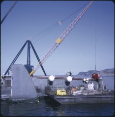 A barge in front of the Wahine wreck and a crane behind the TEV Wahine wreck lifting a generator
