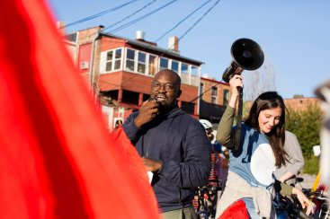 Vimbayi Kaziboni speaks over a megaphone to an outdoor crowd of bicyclists
