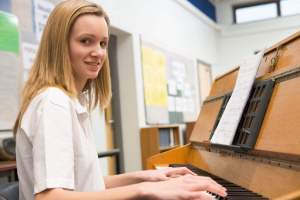 Schoolgirl playing piano in music class