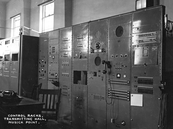"Undated, pre-1961 photo. ""The right hand rack has a double panel of alarm 'grasshopper' fuses near the top, then a storage unit for the HOR's coil sets. The next rack to the left has line monitoring and patch panels. The next rack has an HRO monitor receiver and speaker, plus what I think is the intercom to the receiving station. In the next rack is a control panel for a Collins auto-tune transmitter. I cannot identify the other 3 racks' contents. To the left of the racks is the oldest of 3 Collins 231 3KW auto-tune transmitters."