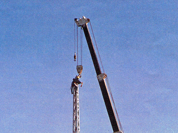 A rigger atop the 100' northwest tower, attaches the crane's hook to the tower.