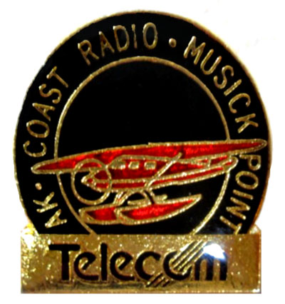 Lapel pin labelled AK COAST RADIO MUSICK POINT with the Telecom logo. Date and circumstances unknown