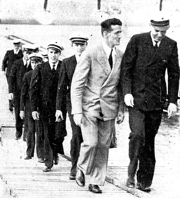 Harold Gatty (Pan American representative in Auckland) escorts Captain Edwin Musick and his crew to the dais, 30 March 1937