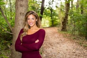 Kristin Gavaza Teacher Headshot Background in wooded path, maroon shirt