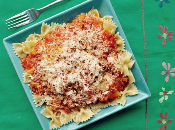 a blue shallow bowl full of bow tie pasta and roasted red pepper sauce and parmesan