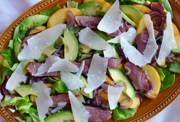 Large shallow plate of butter lettuce, duck breast, peach, and avocado salad.